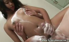 Soapy asian masseuse tugging client in bathroom